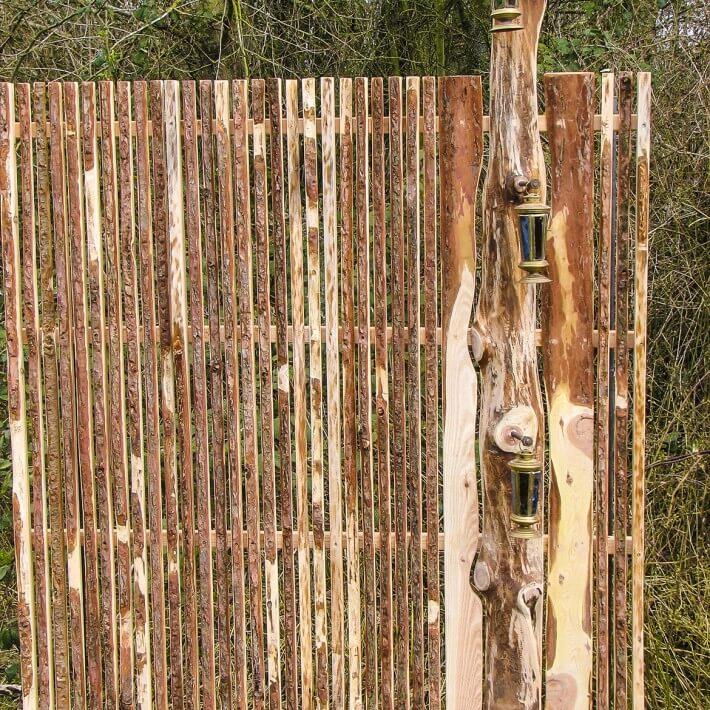 Lichtzaun mit Laternen, rostigen Eisenbolzen und Lärchenholz